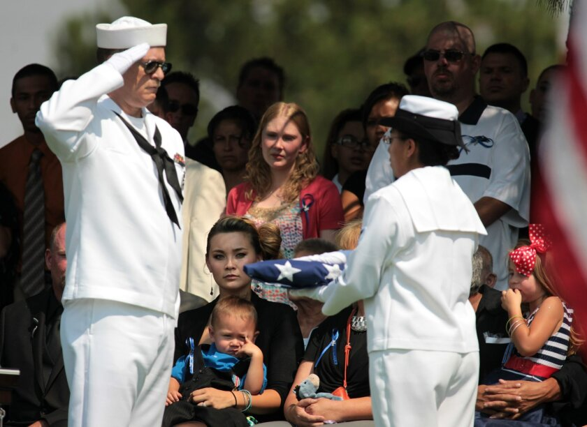 FILE - In this Aug. 3, 2012 file photo, Chantel Blunk, center, the wife of Aurora, Colo. movie theater shooting victim Jonathan Blunk, holds their son Maximus, 2, and daughter Hailey, 4, right, as a U.S. flag is prepared to present to her during a graveside service in Reno, Nev. Jonathan Blunk, 26,