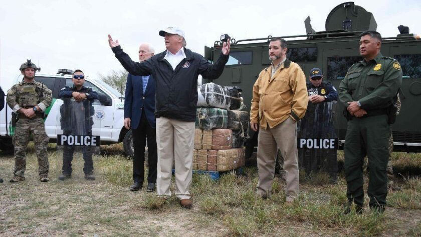 President Trump is flanked by Sens. Ted Cruz and John Cornyn and Border Patrol agents while speaking about the government shutdown and his proposal for a wall in McAllen, Texas, on Jan. 10.