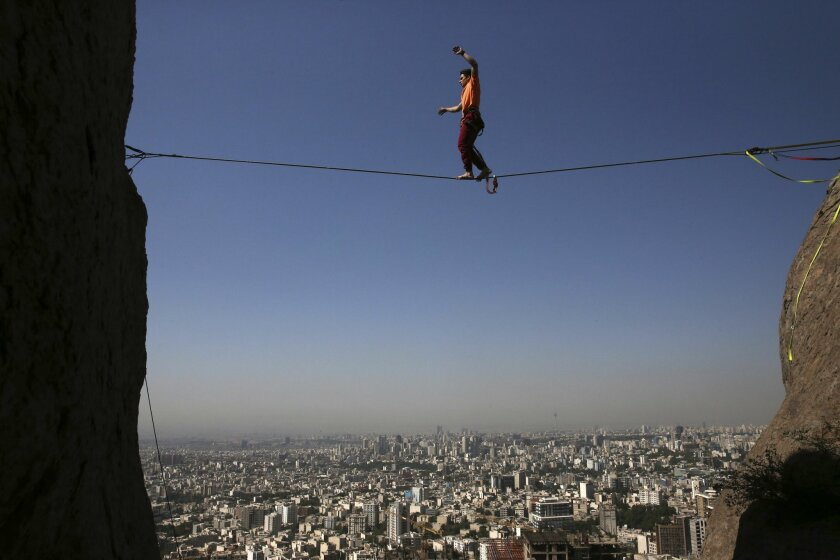 In this picture taken Friday, May 22, 2015, Iranian Hamed Heidari walks across a slackline anchored between two rocks during practice in the mountains overlooking Tehran, Iran. Heidari is one of a growing number of Iranians embracing the extreme sport of slacklining -- a high-wire walk on a flat li
