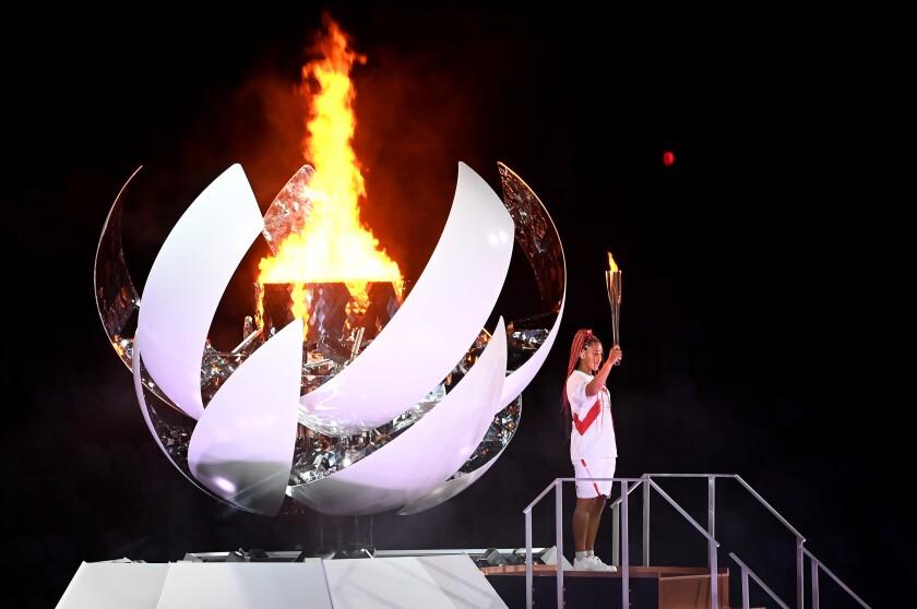 Naomi Osaka allume la torche olympique lors de la cérémonie d'ouverture des Jeux de Tokyo.