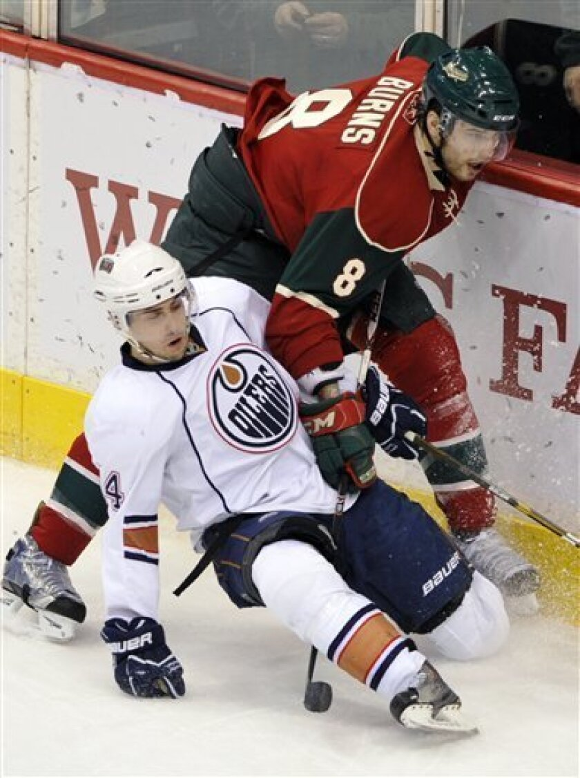 Edmonton Oilers' Jordan Eberle, left, falls as he gets tangled up with Minnesota Wild's Brent Burns during the first period of an NHL hockey game on Thursday, March 31, 2011, in St Paul, Minn. AP Photo/Jim Mone)