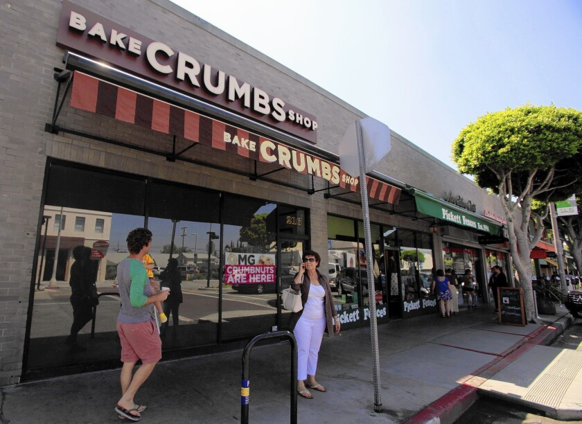 People walk past the closed Crumbs Bake Shop on Larchmont Boulevard in Los Angeles, the chain's last remaining store in the L.A. area.
