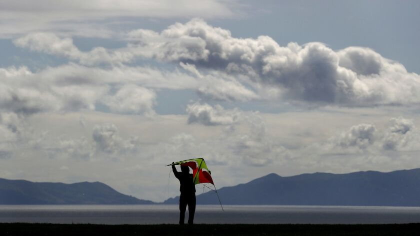 Ted Rivera prepares to fly a kite on a cloudy and breezy day at Angels Gate Park in San Pedro.