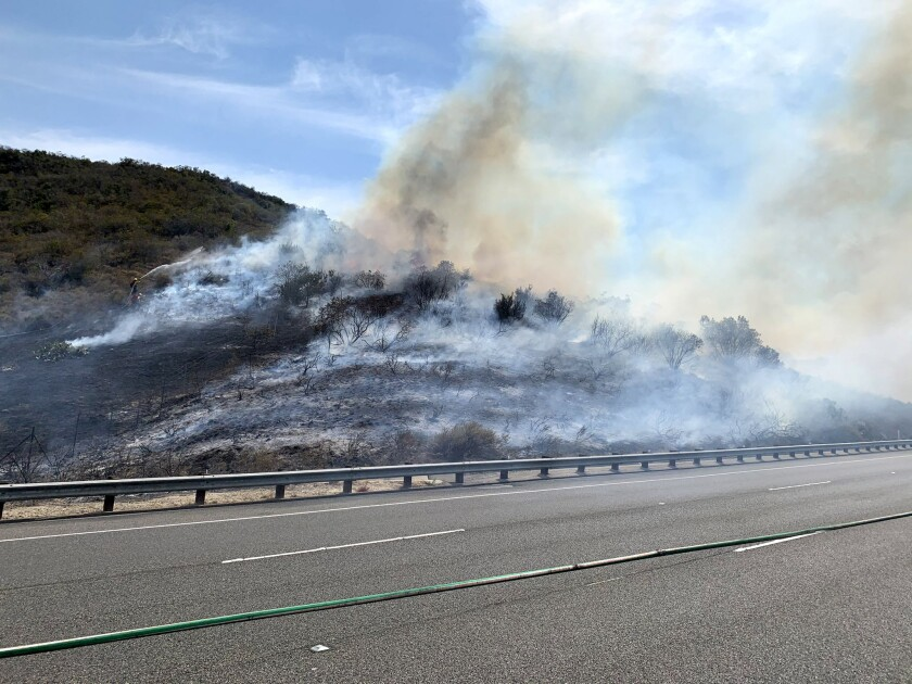Firefighters on scene of a vegetation fire on the SB 73 just west of the 133 on Wednesday.