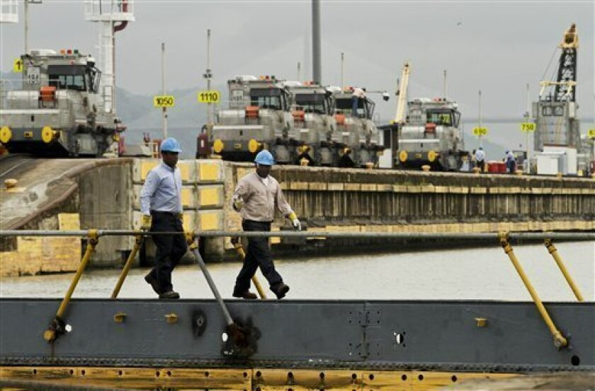 Panama Canal workers walk on a bridge backdrpped by locomotives waiting for ships to guide through the Miraflores Locks in Panama City, Wednesday, June 12, 2013. Nicaragua is plowing ahead with a plan to dig a Chinese-funded rival to the Panama Canal across the midriff of the country, fast-tracking