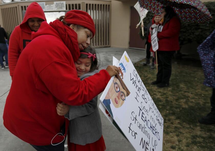 Pacoima, CA January 15, 2019: Kindergartener Alice Garrido, 5, right, hugs her kindergarten teache