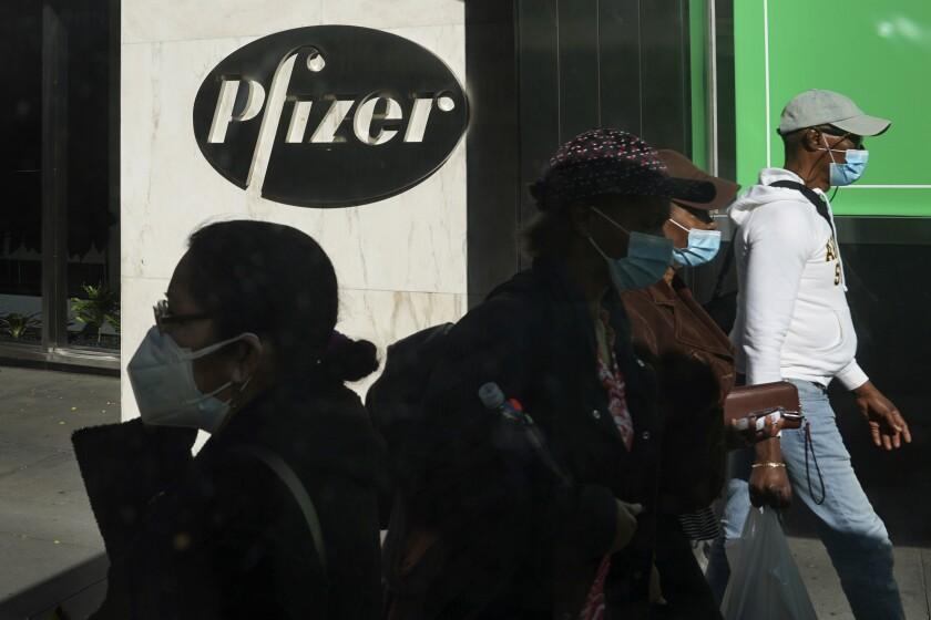 Pedestrians walk past Pfizer world headquarters in New York.