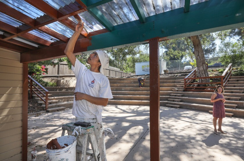 Painter Alder Flores applies finishing touches to an awning at the outdoor amphitheater of the new middle school campus of The Rhoades School in Encinitas. At right is Regina McDuffie, the school's director.
