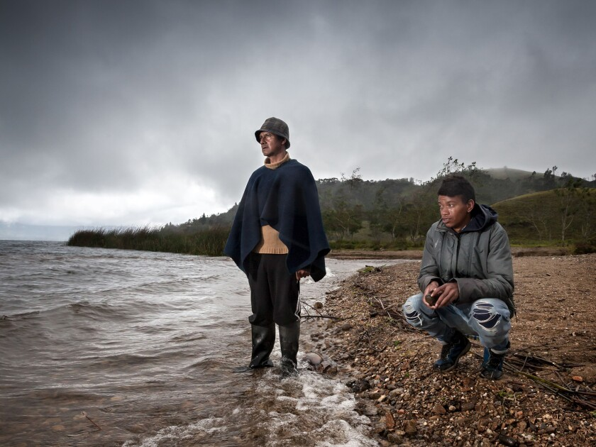 A young man in ripped jeans crouches on a rocky ocean shore alongside a man in wading boots standing in the water.