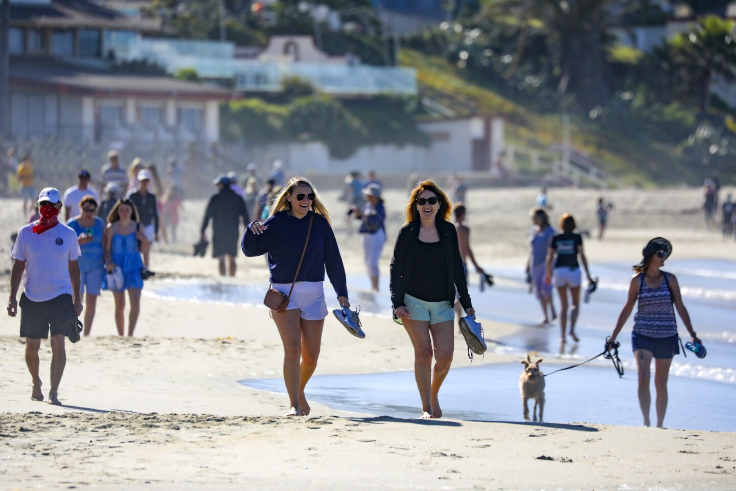 LAGUNA BEACH, CA - MAY 05: People stroll along Laguna Beach on Tuesday morning as city with State's blessings reopened its beaches for active use only. The first phase of the reopening includes 6-10 a.m. hours Mondays through Fridays. in Laguna Beach on Tuesday, May 5, 2020 in Laguna Beach, CA. (Irfan Khan / Los Angeles Times)