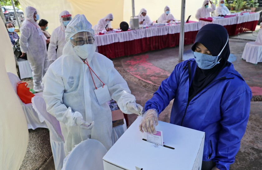 An electoral worker wearing a protective suit as a precaution against the coronavirus outbreak assists a woman to cast her ballot during the regional election at a polling station in Tangerang, Indonesia, Wednesday, Dec. 9, 2020. Indonesia pushed forward with holding previously postponed regional elections on Wednesday amid concerns about the spread of the coronavirus. (AP Photo/Tatan Syuflana)