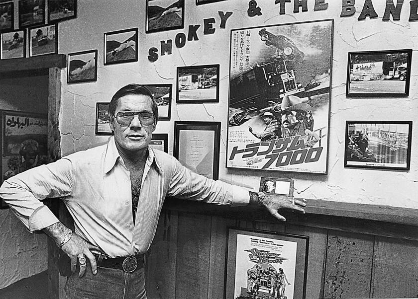 """Hal Needham poses with photos and posters from """"Smokey and the Bandit,"""" one of the films he directed."""