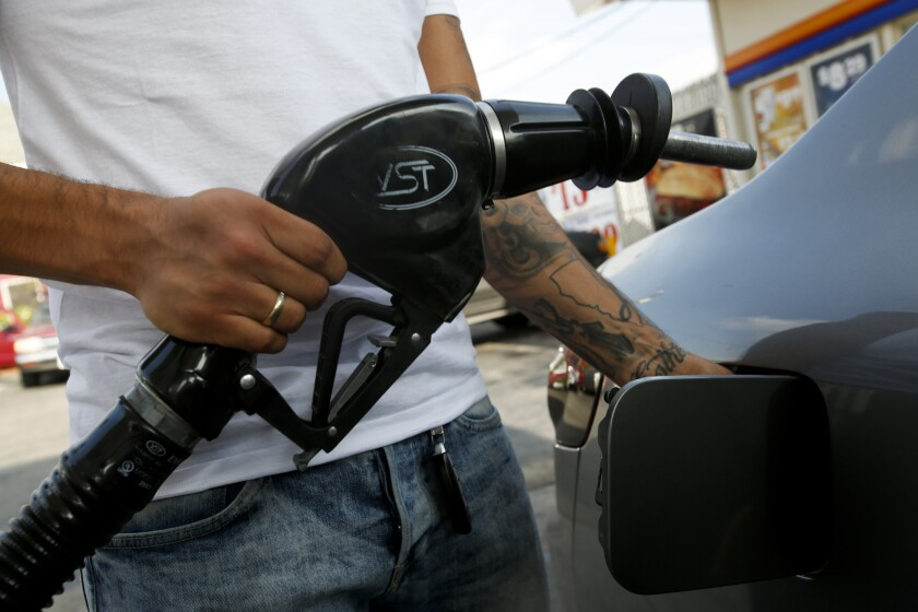 A customer fills up his car's gas tank at an Arco station on Whittier Boulevard in Los Angeles on Nov. 14, 2014.
