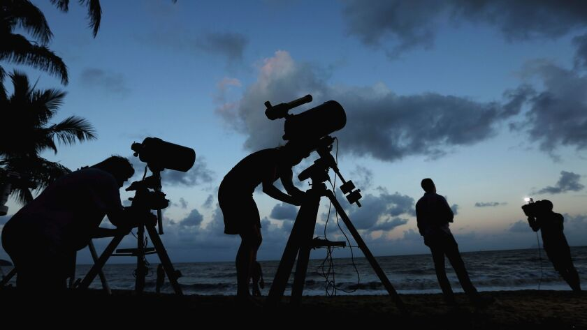 Telescopic cameras and computer equipment are set up on Palm Cove beach in Cairns, Australia to live
