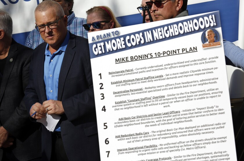 L.A. Councilman Mike Bonin stands next to a poster that illustrates his 10-point plan at a news conference outside the LAPD Ahmanson Recruit Training Center in Los Angeles.