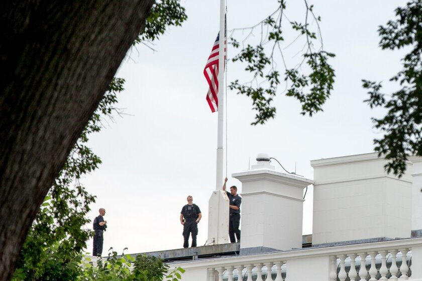 The American flag is lowered to half-staff above the White House in Washington, Tuesday, July 21, 2015, to honor the five U.S. service members who were killed by a gunman in Chattanooga, Tenn. last week. President Obama has ordered flags at all military and federal buildings and grounds through out the United States to remain at half-staff through July 25th. (AP Photo/Andrew Harnik)