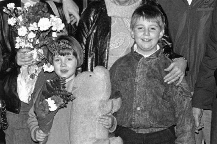 In this image provided by Anna Tabakh, she and her older brother, Ilya, stand with their family after arriving at the Kansas City, Mo. airport in December 1990, a year before the collapse of the Soviet Union. At age 5, Anna didn't know a word of English, en route with her parents from the Soviet Union to a new home in Kansas City, Mo. The beginning was traumatic, she says, now 27, but the transition to American life was relatively smooth - a result that some social scientists would say was partl