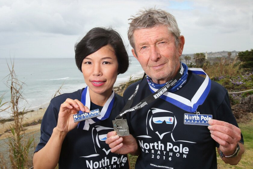Portrait of marathon runners Vivian Lee, left, and Michel Ribet above the beach in Del Mar wearing their medals earned for completing the North Pole Marathon, one of the world's toughest foot races.