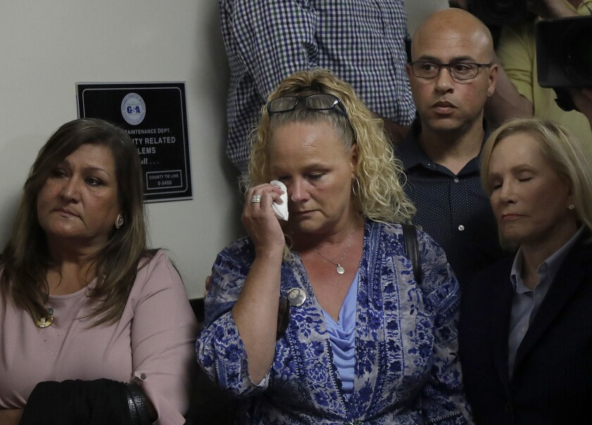Kimberly and David Gregory, center and top right, the parents of Michela Gregory, a victim of the 2016 Ghost Ship warehouse fire, sit next to attorney Mary Alexander, right, during a news conference at a courthouse in Oakland.