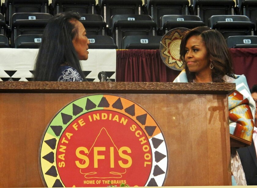 """Santa Fe Indian School Principal Felisa Gulibert, left, thanks first lady Michelle Obama for her commencement address to the school's graduates in Santa Fe, N.M., Thursday, May 26, 2016. Obama told graduates to take pride in their history and cultures at a time when she says the """"loudest voices in"""