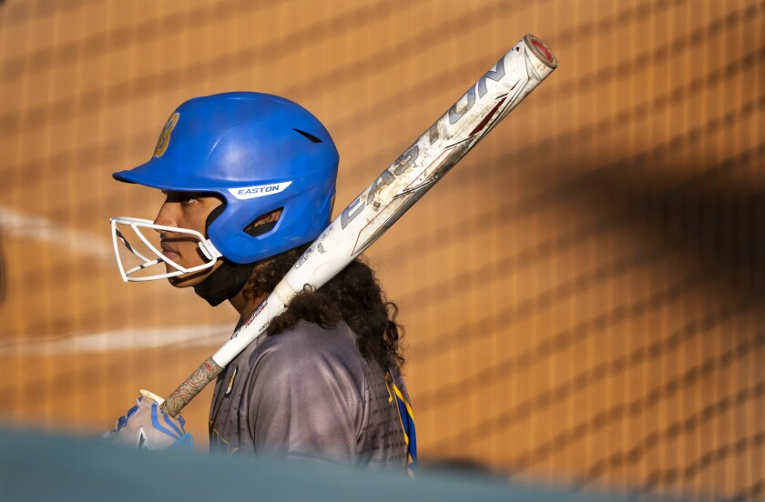 A softball players waits in the on-deck circle.