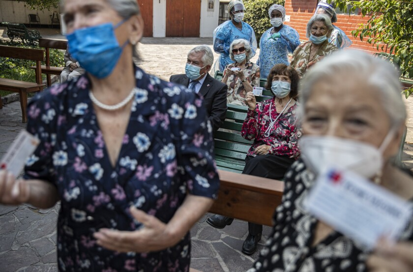 Reisents pose for a photo with their updated vaccination cards and Chilean Health Minister Enrique Paris after they were inoculated with their second dose of the Sinovac COVID-19 vaccine, on the patio of a home for the elderly in Santiago, Chile, Friday, March 5, 2021. No other country in Latin America has had anything near Chile's success in vaccinating its population. (AP Photo/Esteban Felix)