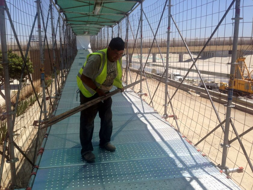A workman put finishing touches last week on a temporary access structure for the new PedWest pedestrian entrance at the San Ysidro Port of Entry.