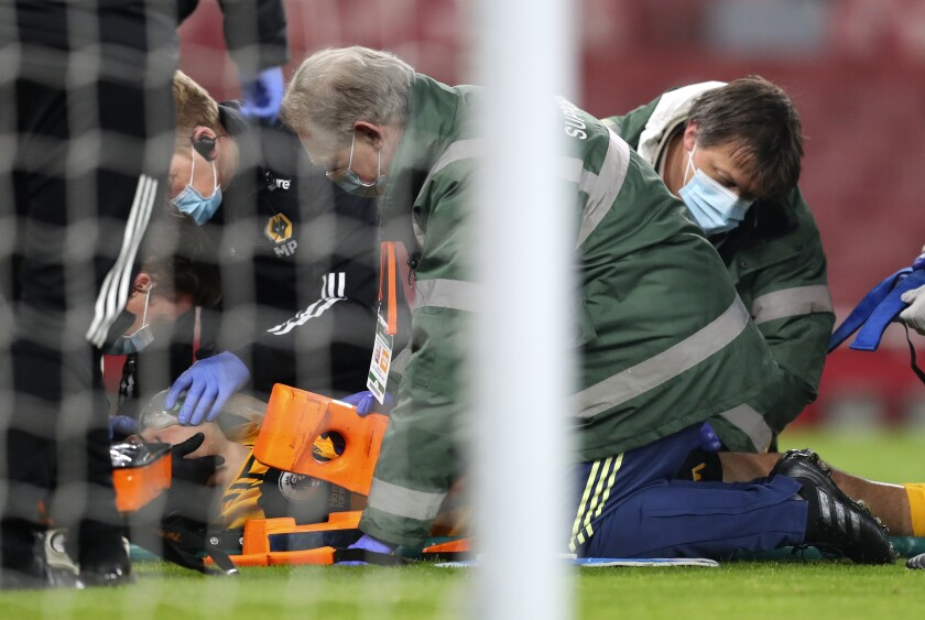 Wolverhampton Wanderers' Raul Jimenez receive treatment from medical staff after a head clash with Arsenal's David Luiz during the English Premier League soccer match between Arsenal and Wolverhampton Wanderers at Emirates Stadium, London, Sunday, Nov. 29, 2020. (Catherine Ivill/Pool via AP)