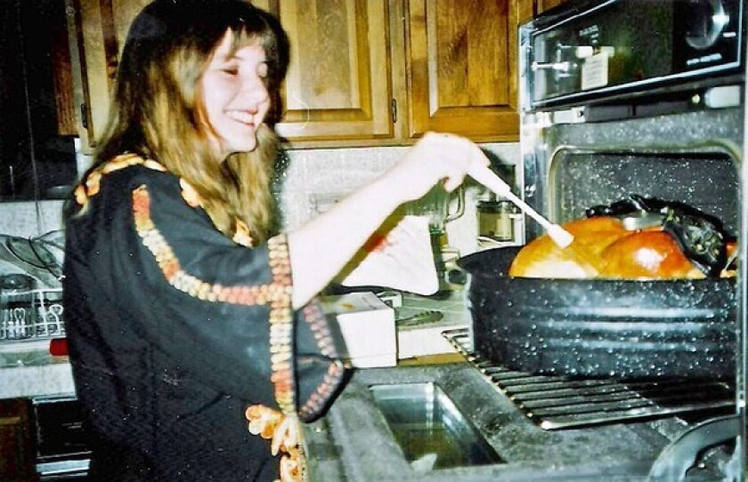 Author Janet Fitch bastes a turkey in her mother's kitchen in the mid-1990s.