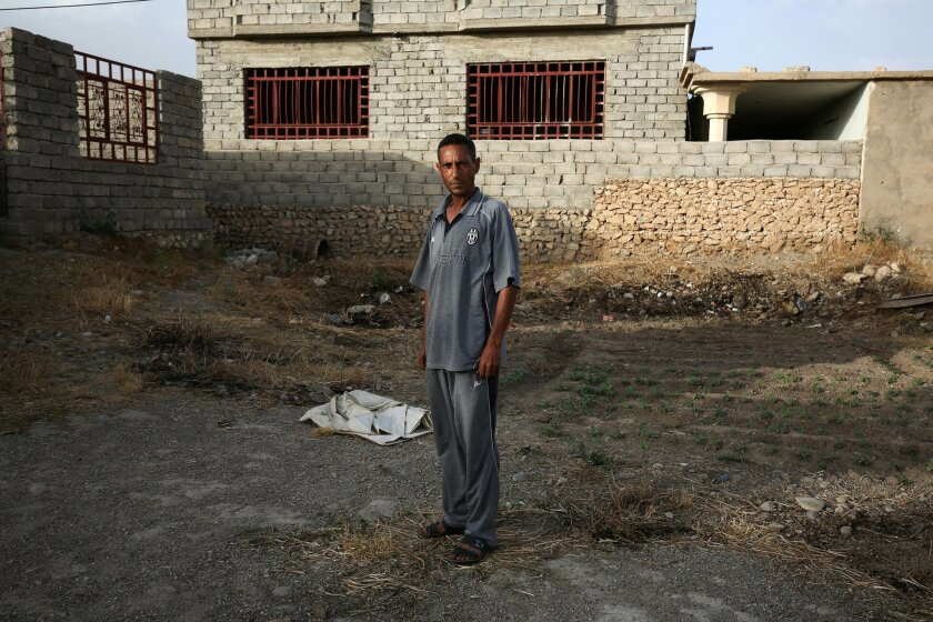 """In this May 26, 2015 photo, Bilal Abdullah poses for a portrait in the village of Eski Mosul in northern Iraq, nearly a year after Islamic State militants took over the village. In the Islamic State's realm, a document testifying that one has """"repented"""" from a heretical past must be carried at all"""