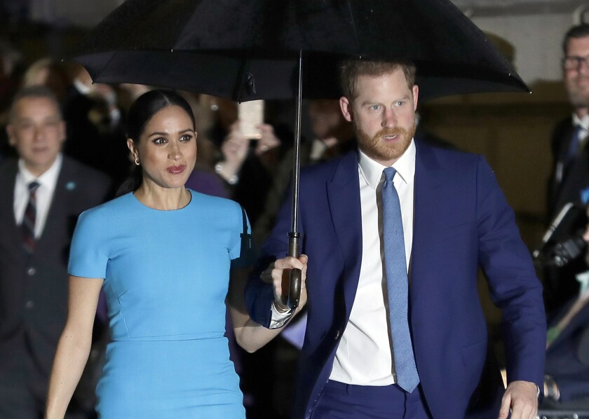 Meghan and Prince Harry walking with an umbrella