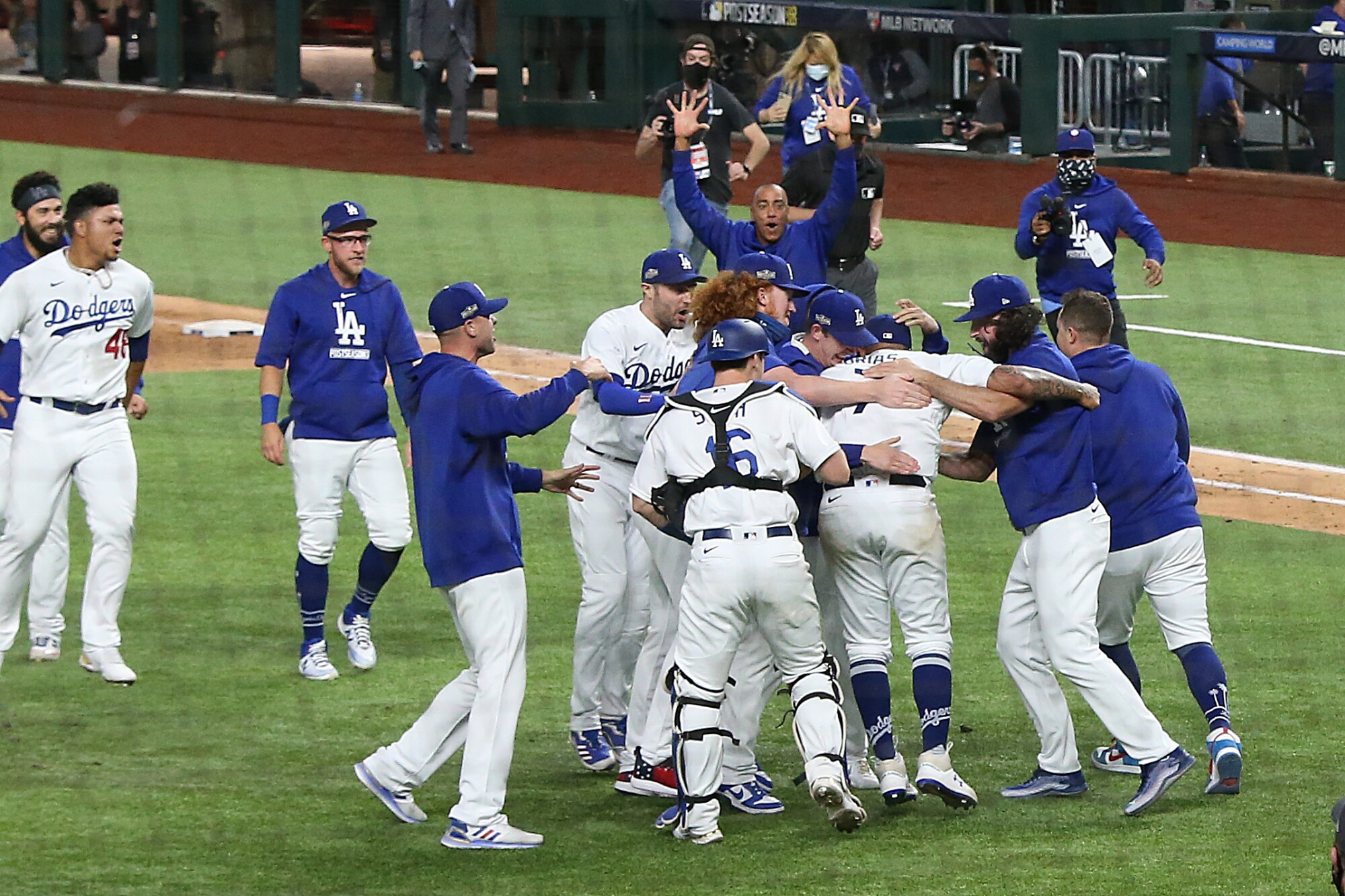 The Dodgers run onto the field, embracing and slapping backs.