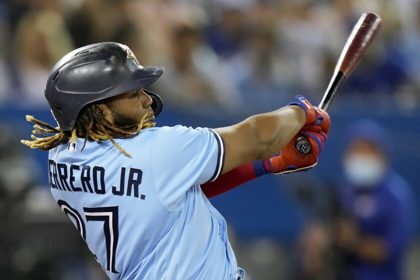 Toronto Blue Jays designated hitter Vladimir Guerrero Jr. (27) hits a two-run home run against the Baltimore Orioles during second-inning baseball game action in Toronto, Sunday, Oct. 3, 2021. (Frank Gunn/The Canadian Press via AP)