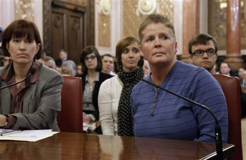 FILE - In this Feb. 5, 2013 file photo, Illinois Sen. Heather Steans, D-Chicago, far left, Bloomington, Ill., resident Danielle Cook, front center, who is in a civil union with her partner of many years, Suzie Hutton, back left, and their 15-year-old son Caleb, right, listen to lawmakers while testifying during a Senate Executive Committee hearing at the Illinois State Capitol in Springfield, Ill. The Illinois Senate is expected to vote on the bill to end Illinois' ban on same-sex marriage Thursday, Feb. 14, 2013. (AP Photo/Seth Perlman, File)