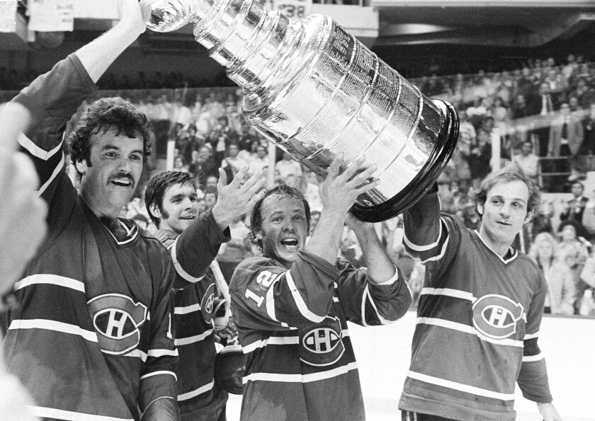 Montreal Canadiens captain Yvan Cournoyer, center, carries the Stanley Cup with teammates.