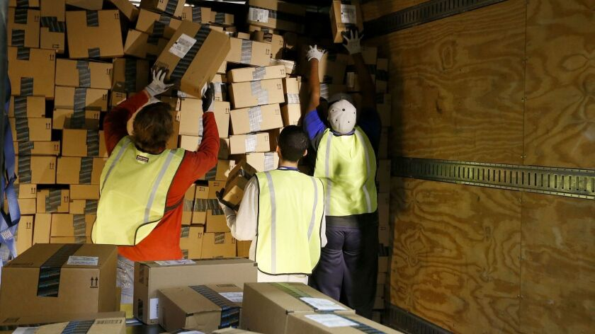 """Amazon.com employees pack up an outbound shipping truck at an Amazon.com Fulfillment Center on """"Cybe"""