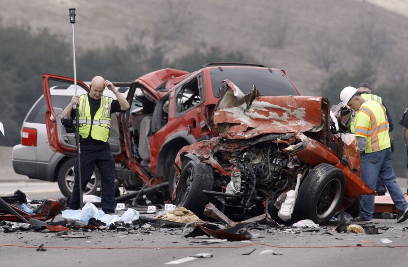 Steve Taggart, left, of the California Highway Patrol takes measurements at the wreckage of a car crash on the westbound 60 Freeway in Diamond Bar on Feb. 9 that left six people dead.