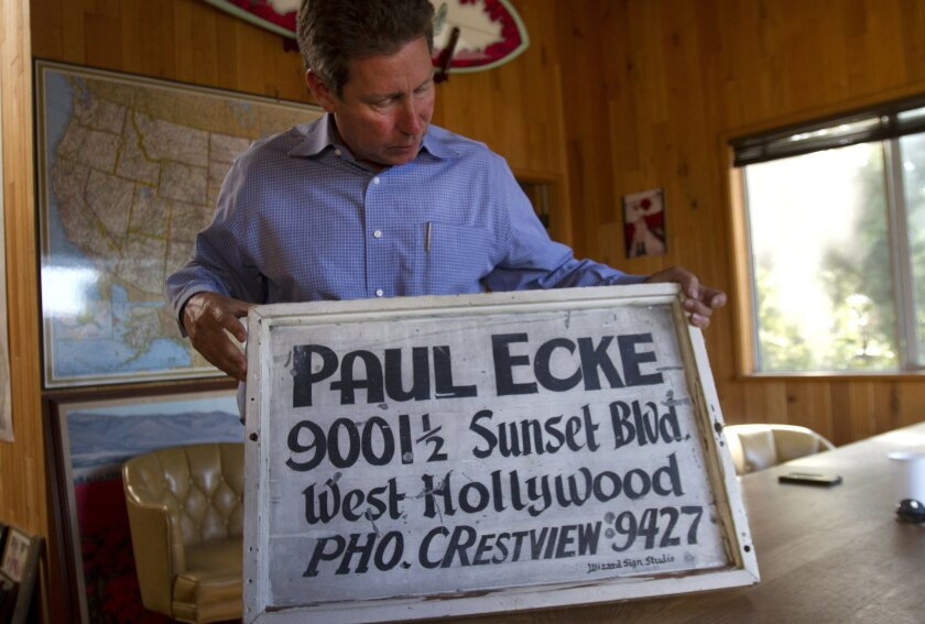 Paul Ecke III, former owner of Ecke Ranch poinsettia farm, shows a sign from the 1920s for one of his family's old poinsettia packing shed in Los Angeles. It was among the many artifacts he discovered in the past year while preparing his family's records for an archiving project at Cal State San Marcos. This photo was taken in April 2013.