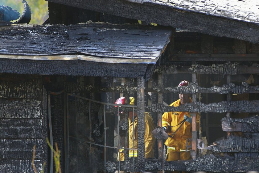 Investigators inspect the home damaged from a house fire that broke out around 4:53 am Monday morning in Bonita. One person was killed and four people were injured.