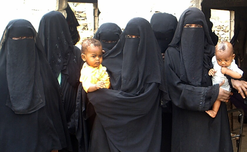 """Women who are descendants of African slaves hold their children as they gather in the village of Aslam in northern Yemen on July 15, 2010. Many are still fighting against the stigma of their former status as """"slaves"""" and have familiy members still living in bondage."""
