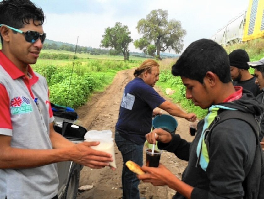 Good Samaritan Adrian Rodriguez, center background, in June gives Central American migrants beverages in Tequixquiac, Mexico. Rodriguez was recently slain.