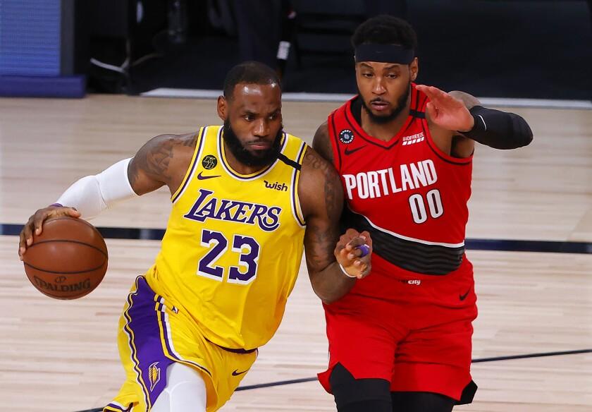 Lakers forward LeBron James drives against Portland Trail Blazers forward Carmelo Anthony.