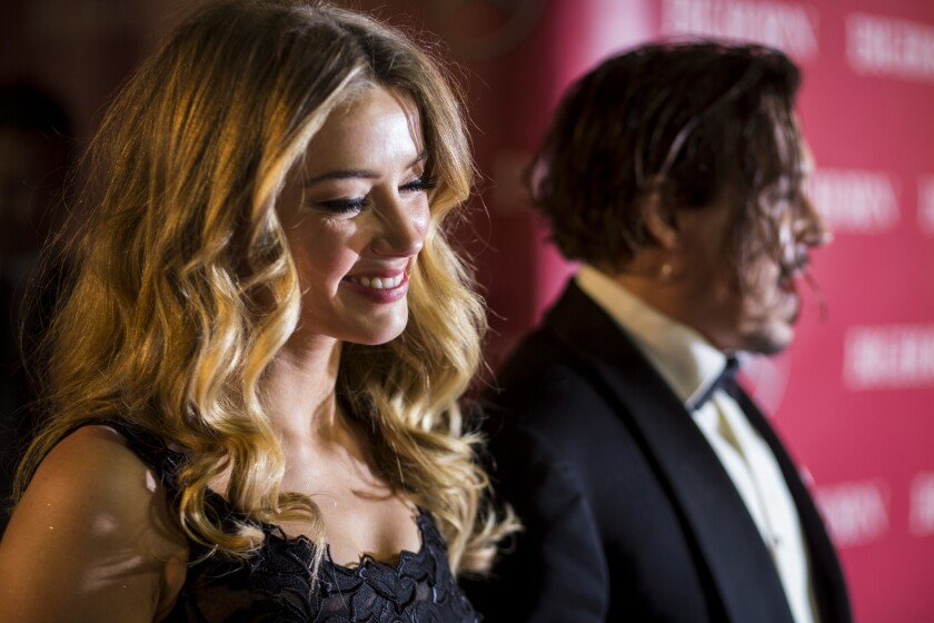 Johnny Depp and Amber Heard, shown at the 2015 Palm Springs International Film Festival Awards Gala, have reached a divorce settlement.