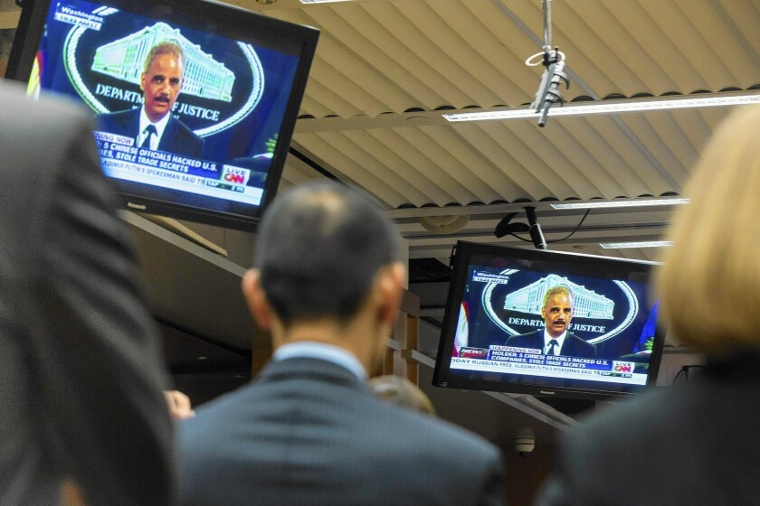 Justice Department staff members watch as Atty. Gen. Eric H. Holder Jr. announces the federal indictment of five Chinese military officials for allegedly stealing U.S. corporate trade secrets.