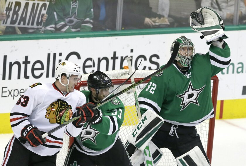 Dallas Stars goalie Kari Lehtonen (32) grabs the puck as teammate Dallas Stars defenseman Alex Goligoski (33) blocks Chicago Blackhawks left wing Brandon Mashinter (53) during the second period of an NHL hockey game Saturday, Feb. 6, 2016, in Dallas. (AP Photo/LM Otero)
