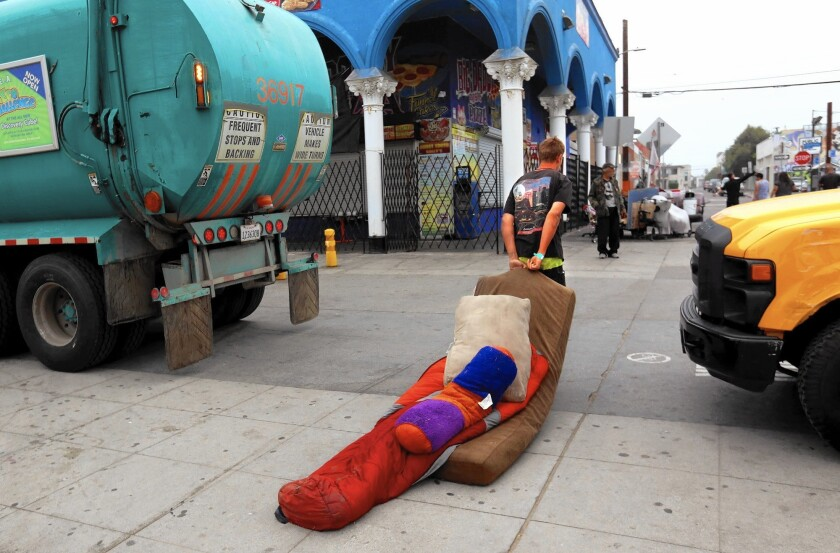 A man drags his bedding after a sweep of homeless encampments on the Venice Beach boardwalk on June 26.