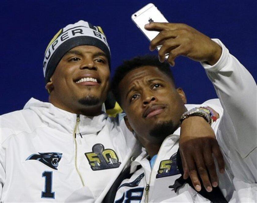 Jonathan Stewart (derecha) de los Panthers de Carolina se saca una selfie con el quarterback Cam Newton durante el día de prensa del Super Bowl el lunes 1 de febrero de 2016 (AP Foto/David J. Phillip)