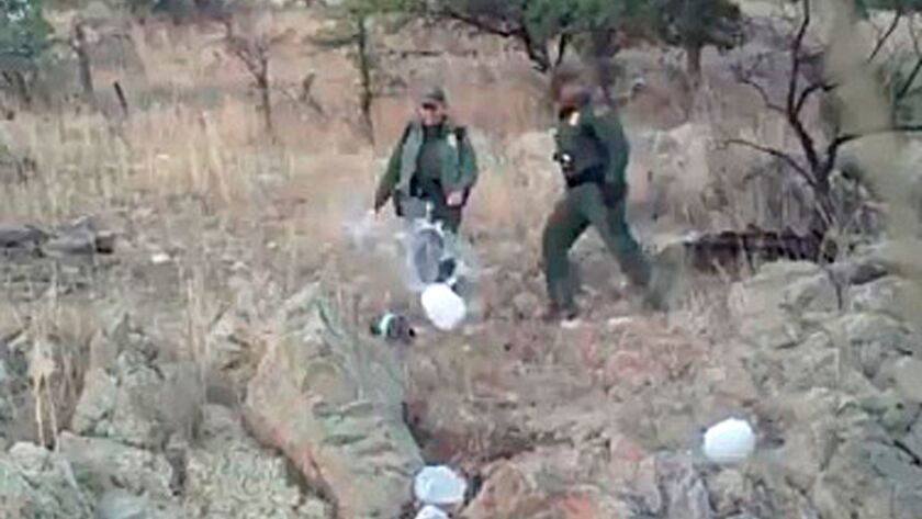 This Jan. 10, 2011, image from video provided by No More Deaths shows Border Patrol agents kicking over water bottles left for those crossing into the U.S. illegally in the Arizona desert.