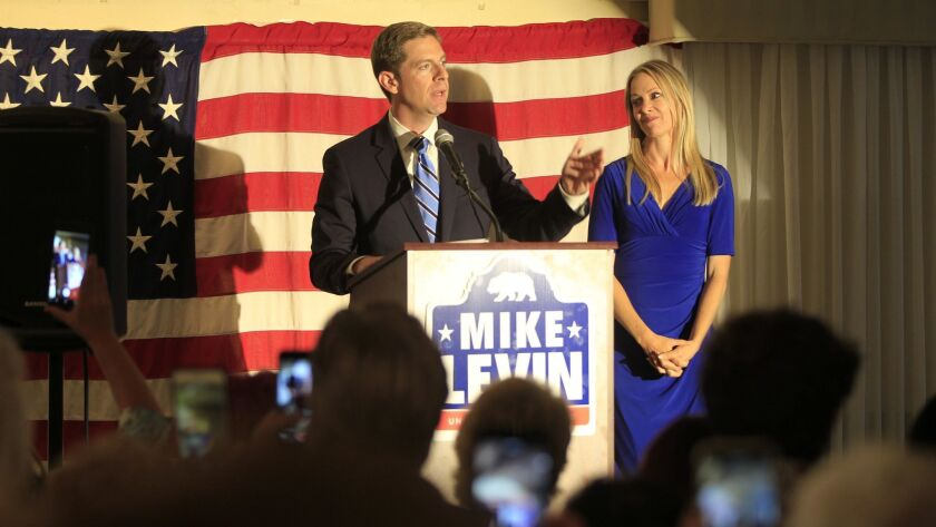 Mike Levin, congressional candidate for the 49th District, with his wife, Chrissy, speaks to supporters on election night. The Democrat won a spot in the general election contest to replace GOP Rep. Darrell Issa.