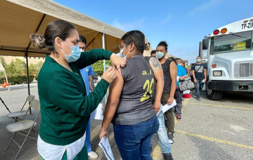 A nurse gives a woman a shot while other people stand in line behind her outside near a bus